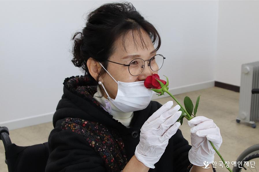 길선옥 씨가 꽃을 코에 갖다대며 향기를 맡고있다.
