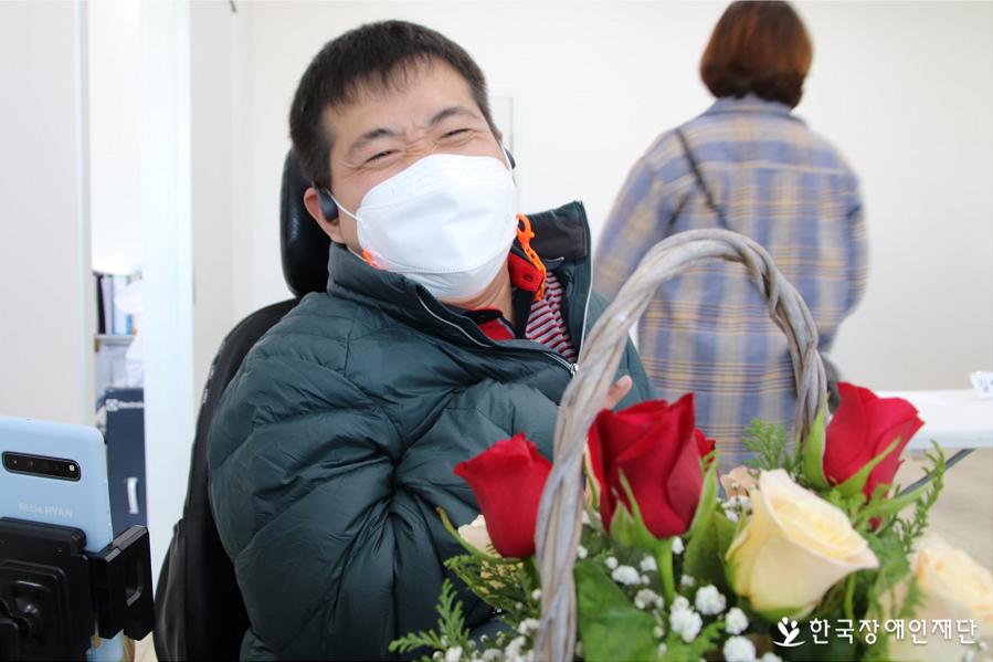 오늘 수업에서 만든 꽃바구니를 보고 웃고있는 조영준씨.